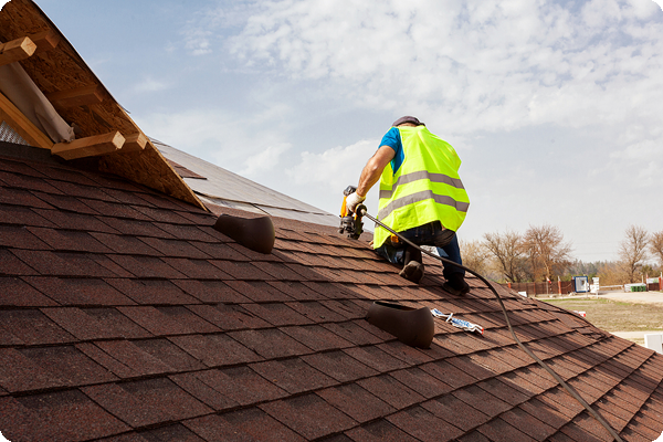 Roofer putting down shingles on a roof.