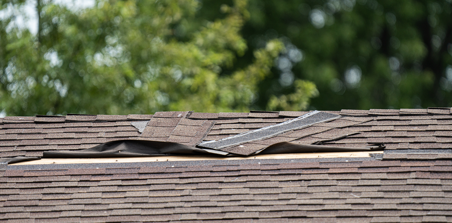 Roof on house with damaged shingles.